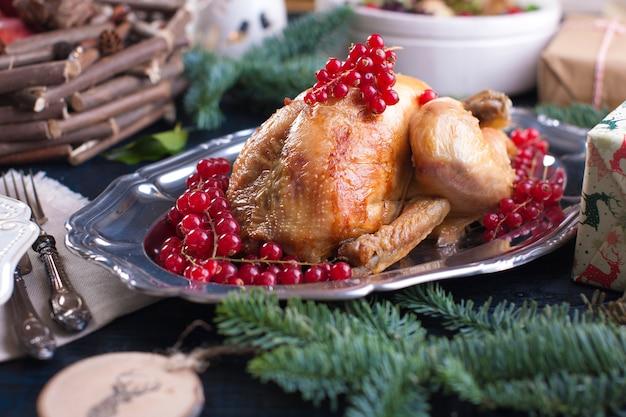 Gebakken kip op een schotel met rode bessen. op een blauwe houten tafel met een hark