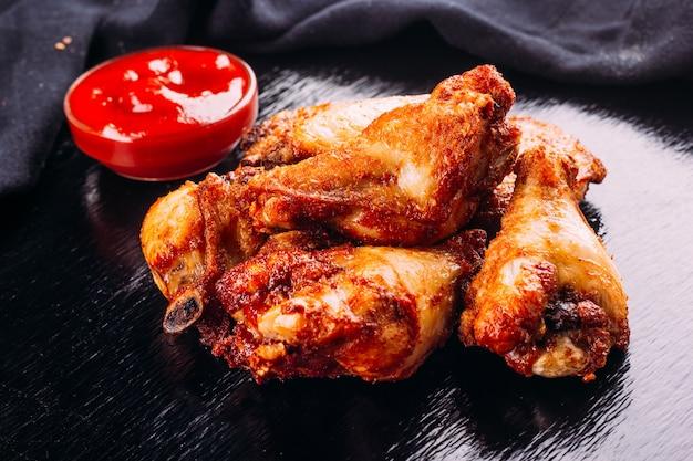 Gebakken kip op een zwarte achtergrond en ketchup ernaast
