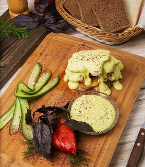 Gebakken kip, visfilet met gesmolten kaas en tomaat, komkommersalade op een houten bord