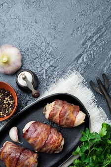 Gebakken kipfilet omwikkeld met spek op een gietijzeren koekenpan op een zwarte