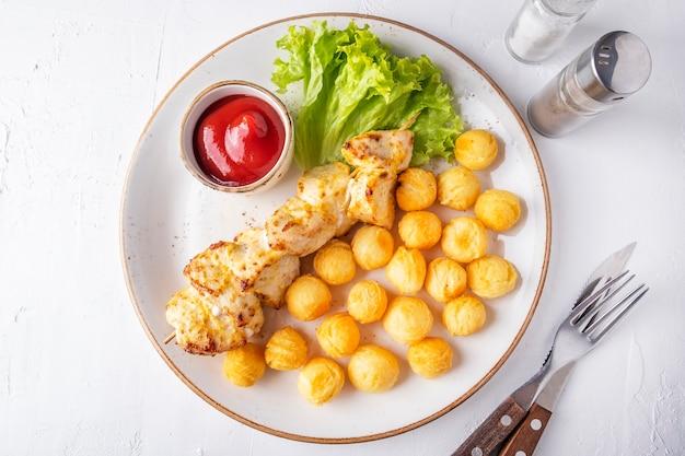 Gebakken kipfilet op spiesjes met aardappelballetjes en ketchup. bovenaanzicht
