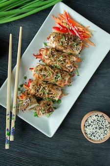Gebakken kipfilet rolletjes met kruiden, schijfjes wortel, paprika op een donkere snijplank. aziatische stijl. de balans van gezond eten. koken. donkere houten tafel.
