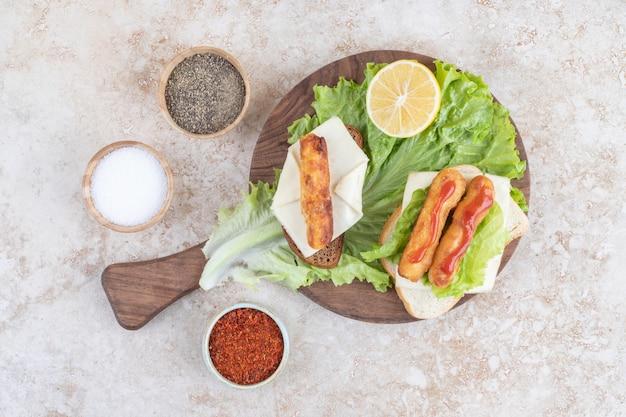 Gebakken kipnuggets en kaasstengels op een houten bord op een stuk slablad.