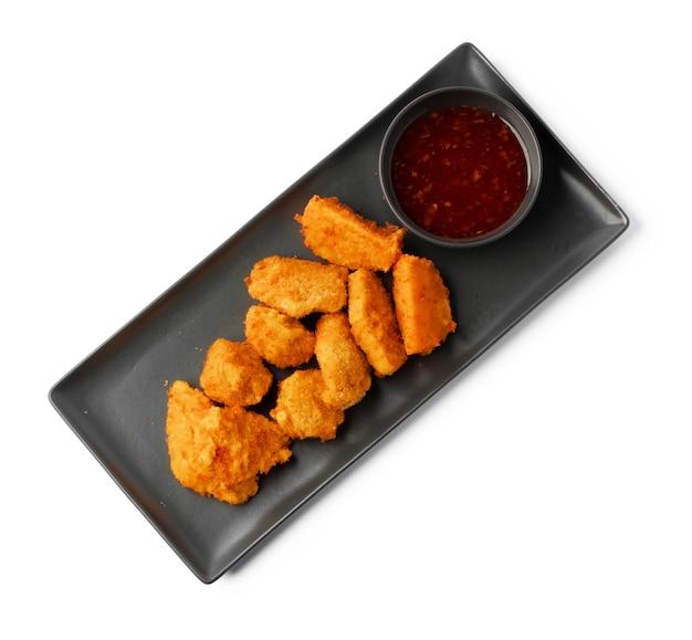 Gebakken kipnuggets geserveerd met saus geïsoleerd op wit