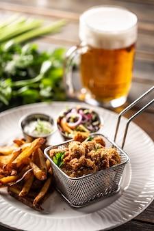 Gebakken kipnuggets met frietjes, dipsaus, salade en bier.