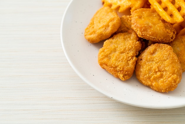 Gebakken kipnuggets met gebakken aardappelen op plaat potatoes