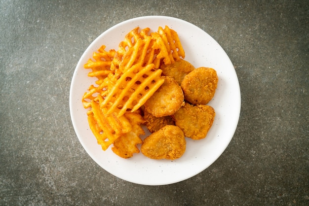 Gebakken kipnuggets met gebakken aardappelen op plaat