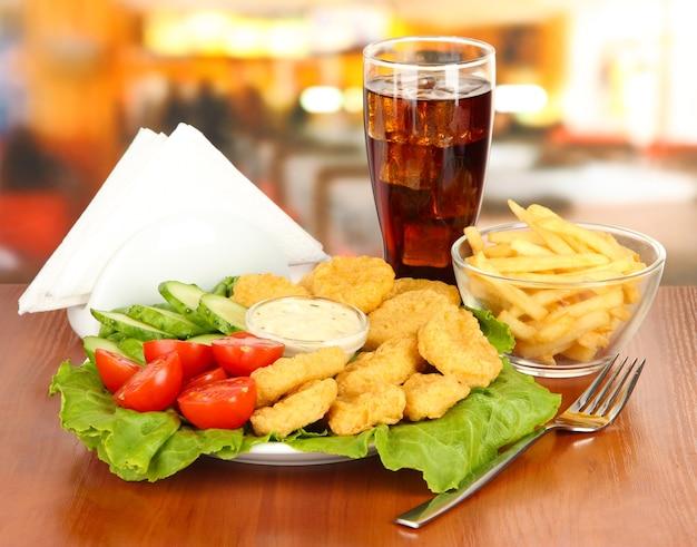 Gebakken kipnuggets met groenten, cola, frietjes en saus op wit
