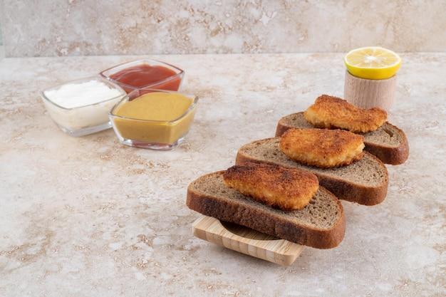 Gebakken kipnuggets op donkere sneetjes brood geserveerd met sauzen.