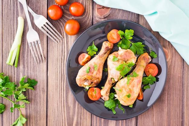 Gebakken kippenbenen in kruiden met tomaten en greens in een plaat op een houten tafel, bovenaanzicht