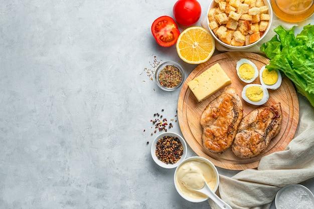 Gebakken kippenborst eieren kaas verse kruiden en croutons op een grijze bureau ingrediënten voor caesar salade