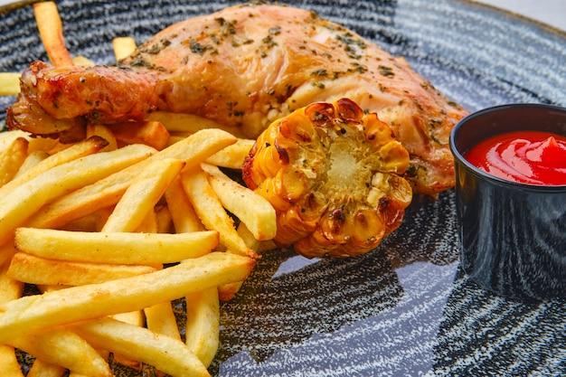 Gebakken kippendij met frietjes bij gegrilde maïs en ketchup
