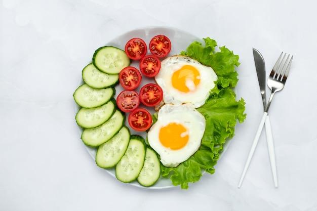Gebakken kippeneieren met groenten op een grijze tafel. ontbijtconcept. bovenaanzicht. voedsel achtergrond in de ochtend. vers gesneden komkommers en tomaten. platliggende compositie. bovenaanzicht.