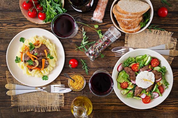 Gebakken kippenlever met groenten en aardappelpuree. salade van kippenlever en ei