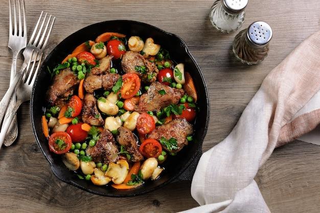 Gebakken kippenlever met plantaardig bijgerecht van tomaten, wortelen, champignons, erwten in een pan