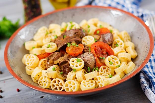 Gebakken kippenlever met tomaat en garnering van pasta