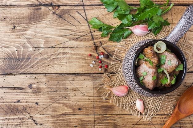 Gebakken kippenlever met ui in een keramische cocotte op een houten rustieke tafel