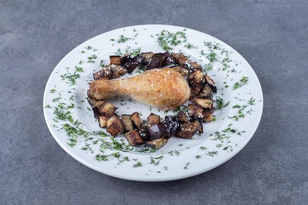Gebakken kippenpoot en aubergine op witte plaat.
