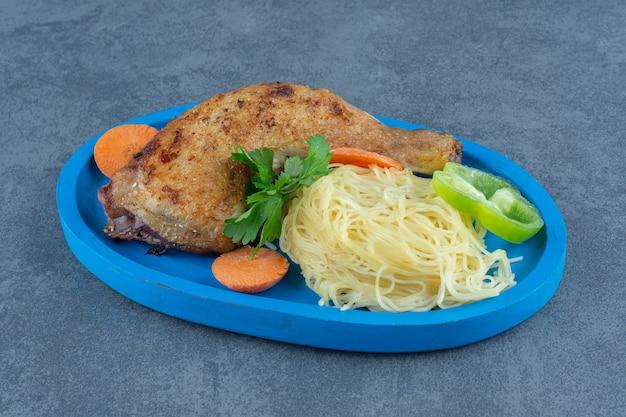 Gebakken kippenpoot en spaghetti op blauw bord.
