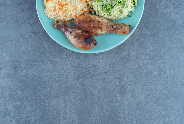 Gebakken kippenpoten en rijst op blauw bord.