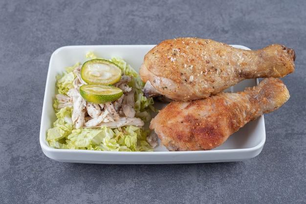 Gebakken kippenpoten en salade op witte plaat.