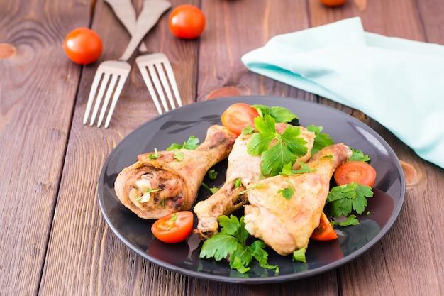 Gebakken kippenpoten in kruiden met tomaten en greens in een bord op een houten tafel