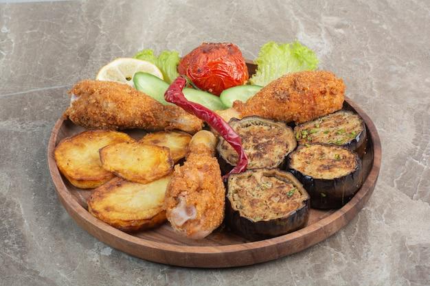 Gebakken kippenpoten met aardappel en aubergine op een houten bord.