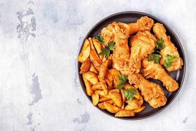 Gebakken kippenpoten met aardappelen.