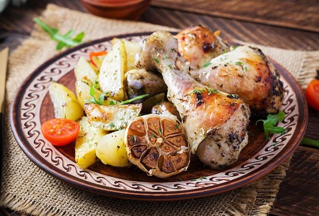 Gebakken kippenpoten met aardappelschijfjes en kruiden.