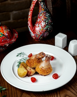 Gebakken kippenpoten met frietjes op tafel