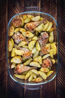 Gebakken kippenpoten met gesneden aardappelen en kruiden. barbecue kippenboutjes. bovenaanzicht, overhead, kopieerruimte.