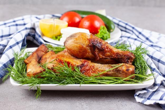 Gebakken kippenpoten met greens op een witte plaat