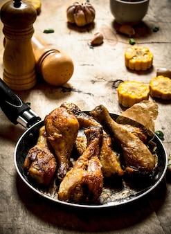 Gebakken kippenpoten met mais en knoflook. op een houten tafel.