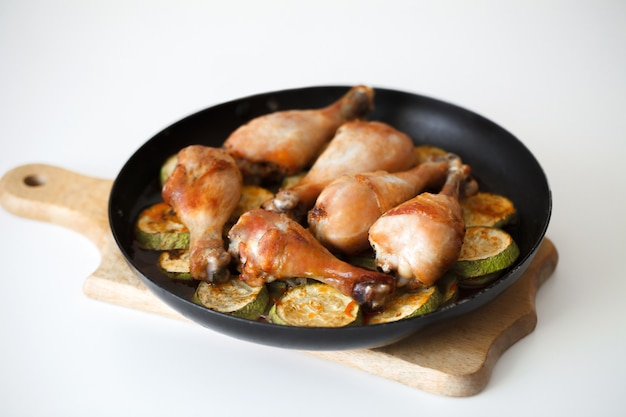 Gebakken kippenpoten met plakjes courgette in een koekenpan op een houten plank wooden