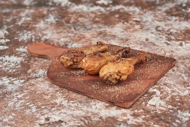 Gebakken kippenpoten op een houten bord.
