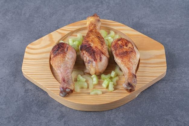 Gebakken kippenpoten op houten plaat.