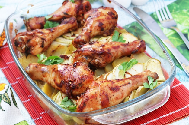 Gebakken kippentrommelstokken met courgette en aardappels in een glasvorm, close-up