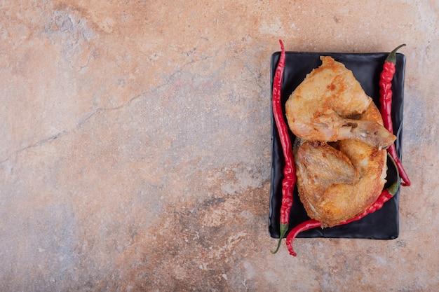 Gebakken kippenvlees in een keramische schotel op marmer.