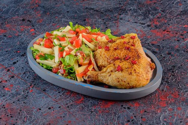 Gebakken kippenvlees met gemengde groentesalade op een donkere achtergrond.