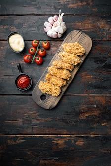 Gebakken kippenvleugels delen op oude donkere houten tafel, bovenaanzicht