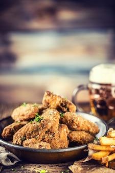 Gebakken kippenvleugels frietjes en bier van de tap op tafel in pub of restaurant.