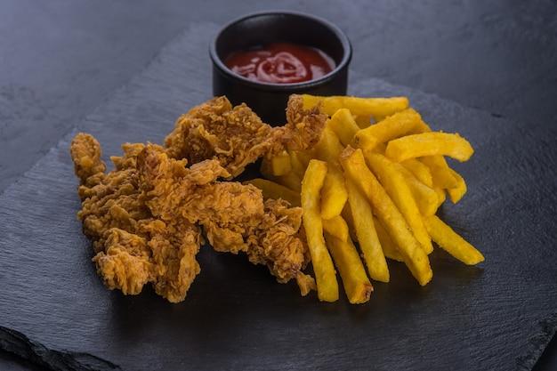 Gebakken kippenvleugels, gepaneerd met frites en ketchup