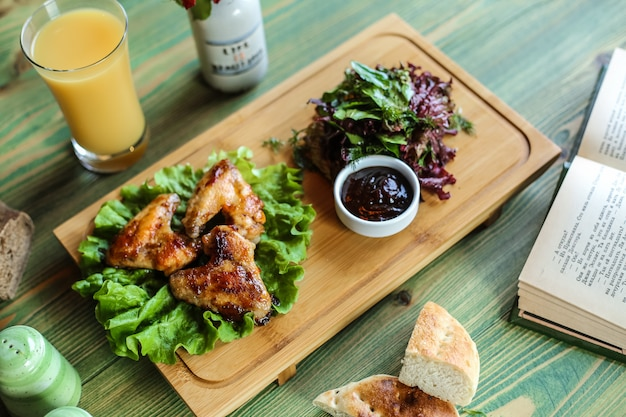 Gebakken kippenvleugels geserveerd met saus en kruiden met sinaasappelsap