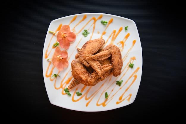 Gebakken kippenvleugels geserveerd op plaat met saus