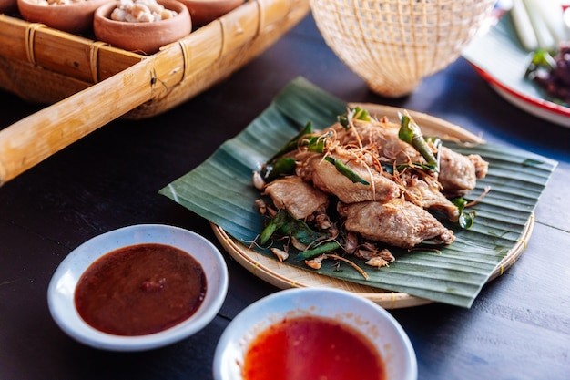 Gebakken kippenvleugels in thaise noordoostelijke stijl met knoflook en kaffir limoenblaadjes.