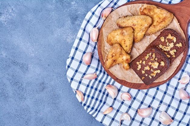 Gebakken kippenvleugels met brood op een houten bord op blauw