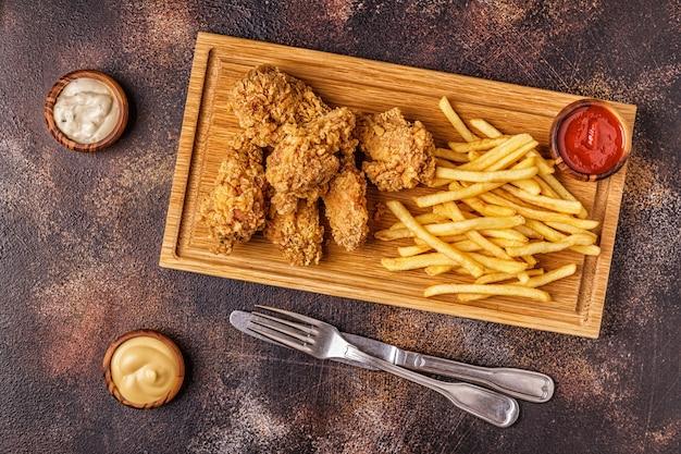 Gebakken kippenvleugels met frietjes, bovenaanzicht.