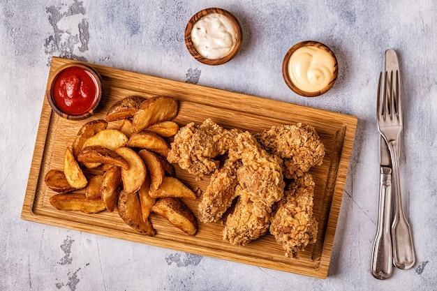 Gebakken kippenvleugels met gebakken aardappelschijfjes, bovenaanzicht.