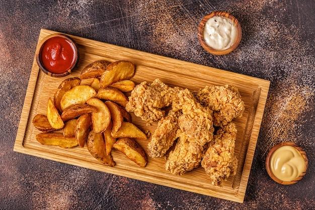 Gebakken kippenvleugels met gebakken aardappelschijfjes