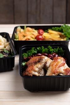 Gebakken kippenvleugels met microgreens, gestoofde groenten in voedselcontainers